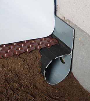 Closeup of a crawl space drainage system installed in Elon