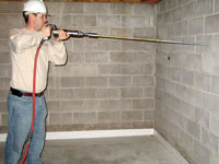 Coring a 1 inch hole in a basement wall to allow for the earth channel anchor rod to pass through.