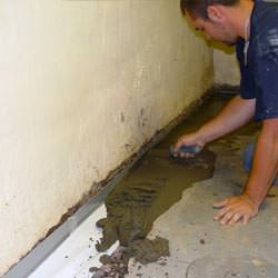 A basement waterproofer installing a perimeter drain system in Galax